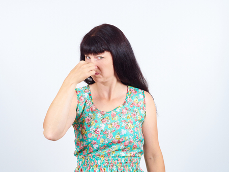A young woman pinches the nose with fingers in disgust something stinks. bad smell, isolated. the expression of the human face. language of the body Stock Photo