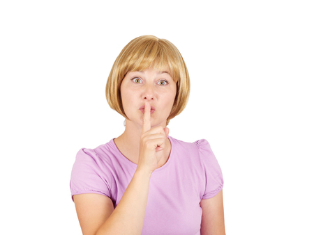 Closeup portrait young woman placing finger on lips. Girl blonde  asking shh, quiet, silence looking at camera isolated on background.