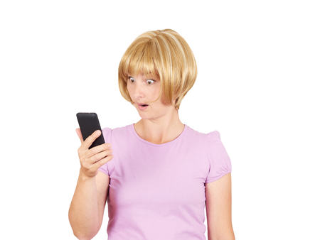 gasping: Closeup portrait anxious  young woman looking at phone seeing bad news. Blonde girl in horror reading sms on your smartphone isolated on  background. Stock Photo