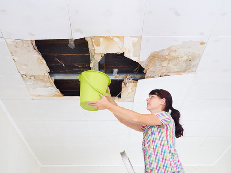 Jonge Vrouw Het verzamelen van Water In Emmer van het plafond. Plafondpanelen beschadigd enorm gat in het dak van regenwater leakage.Water beschadigd plafond. Stockfoto