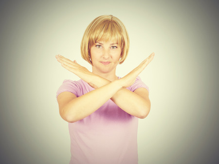 Beautiful young businesswoman with crossed hands. Girl blonde showing stop gesture .  Isolated on background Stock Photo