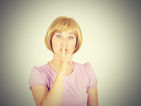 noiseless: Closeup portrait young woman placing finger on lips. Girl blonde  asking shh, quiet, silence looking at camera isolated on background.