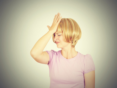 Witless young woman holding her hand to her forehead. Blonde girl forgot. Stupid fool. Isolated on background. Stock Photo