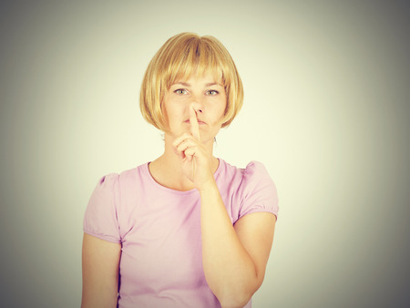 Portrait of a young beautiful woman picks his nose. Isolated on background.