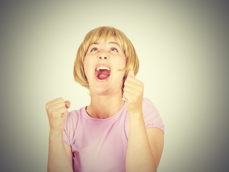 success concept - successful young blonde girl winning a competition with both hands raised up above head. Happy winner.  business woman Stock Photo