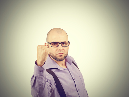 threaten: Angry businessman threaten with a fist . A bald man with a beard in a shirt with suspenders.