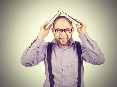 young man holding a book over his head. Bald, bearded businessman. Stock Photo