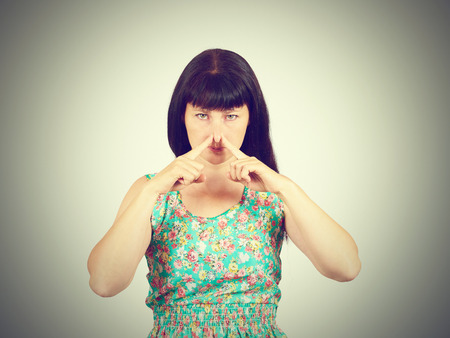 pinches: A young woman pinches the nose with fingers in disgust something stinks. bad smell, isolated. the expression of the human face. language of the body Stock Photo