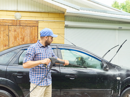 rinse spray hose: Man washing his black car near the house.