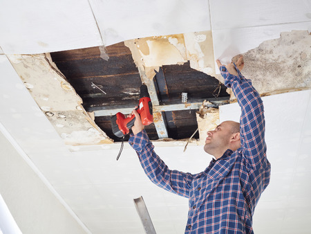 damaged roof: Man repairing collapsed ceiling. Ceiling panels damaged  huge hole in roof from rainwater leakage.Water damaged ceiling .  Stock Photo