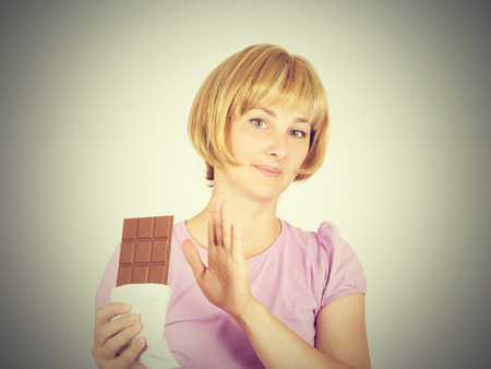 Portrait of young woman eat chocolate though. She exhausted diet. Greed sweet.