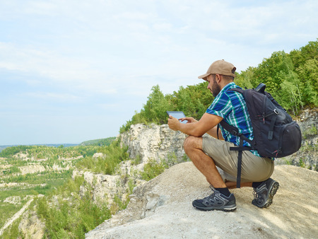 Man tourist uses tablet computer sitting on the edge of a cliff in the mountains. Caucasian male outdoors in nature. Hiker young man with backpack . Stock Photo