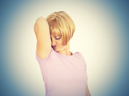 foul: young woman, smelling, sniffing her wet armpit, something stinks, very bad foul odor situation isolated . Negative emotion facial expression reaction Stock Photo