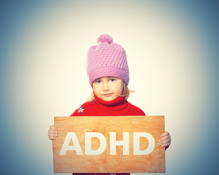 Little girl holding Board with inscription ADHD. Isolated on white background Stock Photo