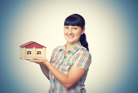 Young woman holding home isolated on a white background. Stock Photo