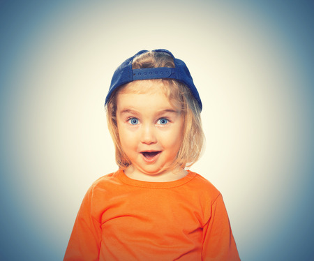 Little Funny girl in baseball cap and orange blouse. Isolated on white background