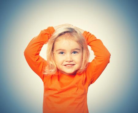 Little Funny girl in orange blouse holding his head. Isolated on white background Stock Photo
