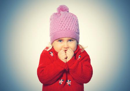 Weinig grappig meisje in cap en rode trui. Geïsoleerd op witte achtergrond Stockfoto - 69087490