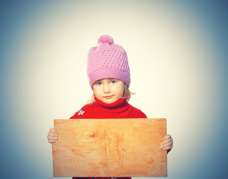 Little girl holding Board for text. Isolated on white background Stock Photo