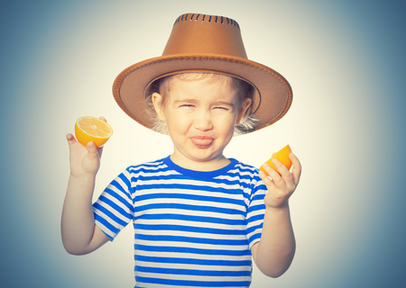 Little Funny girl in striped shirt and hat keeps lemons. Isolated on white background Imagens
