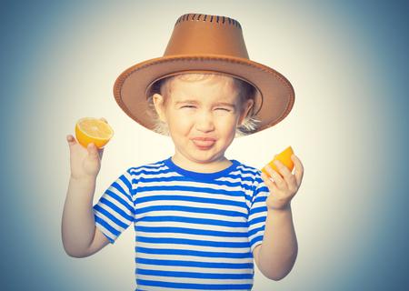 Weinig grappig meisje in gestreepte shirt en hoed houdt citroenen. Geïsoleerd op witte achtergrond Stockfoto - 69087463