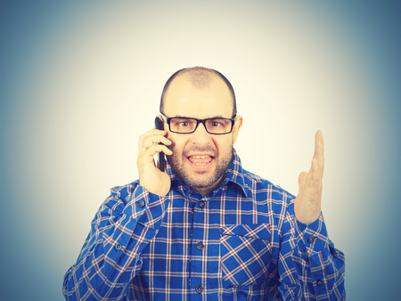 yells: Angry man in glasses yells into  phone. Isolated on white background.