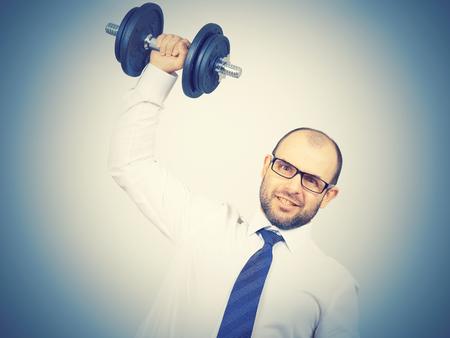 Man Trained businessman raises dumbbell. Isolated on white background