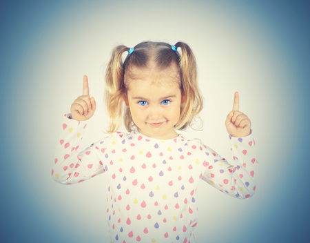 forefinger: little girl wearing  pointing by forefinger to somewhere up isolated