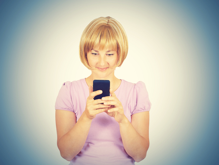 gasping: Young woman reading good news on the phone. Girl smiling blond looking at smartphone. Pleasant SMS. Isolated on background.
