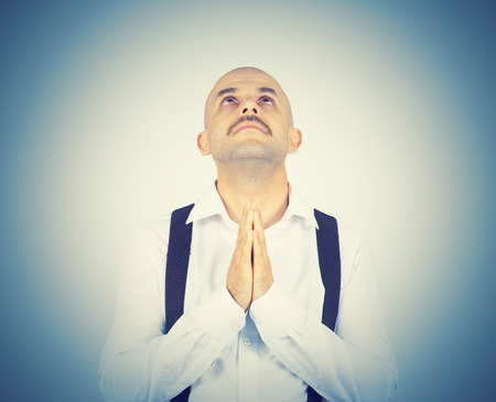 Bald man praying,imploring, hands clasped hoping of miracle isolated on background.
