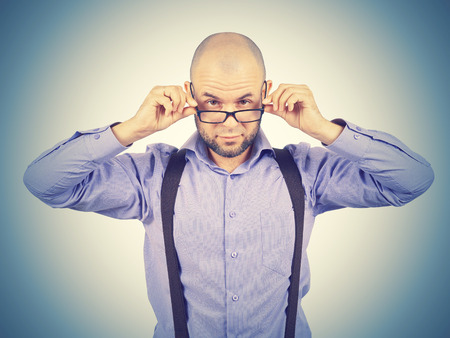 Businessman looking over glasses.bald man in a purple shirt looking through glasses.