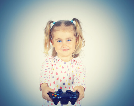 Little girl playing video games with gamepad in the hands. Stock Photo