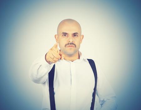 skeptical: Bald businessman pointing at the camera with. Isolated on background. Stock Photo