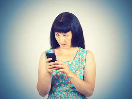 gasping: A young woman reads the SMS, the news on the phone. Emotions, body language, facial expression.