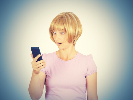 gasping: Closeup portrait anxious  young woman looking at phone seeing bad news. Blonde girl in horror reading sms on your smartphone isolated on  background.