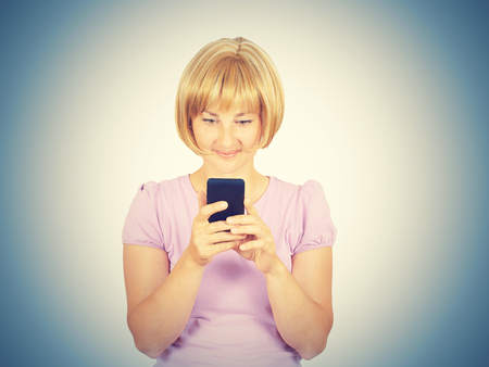 gasping: Young woman reading good news on the phone. Girl smiling blond looking at smartphone. Pleasant SMS. Isolated on background.  Stock Photo