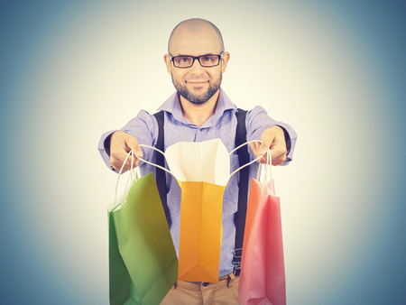 Caucasian man bald, with a beard, glasses with colorful shopping paper bags isolated on white.  Stock Photo