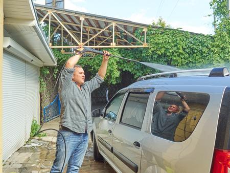 rinse spray hose: Man washing his silver car near the house.