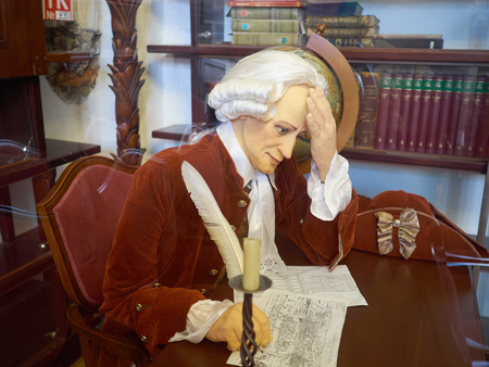 Kaliningrad - April 2017 Russian Immanuel Kant writes a letter with a pen sitting at a table in the library. Wax figure in Kaliningrad. Stock Photo