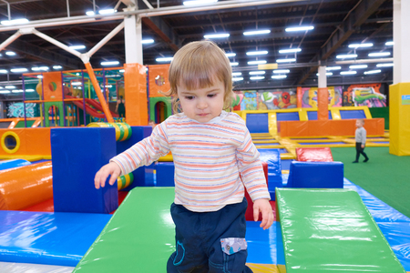 The One Year Old Baby Cute Playing In Indoors Playground. Active Toddler Boy Having Fun At Sport Center.