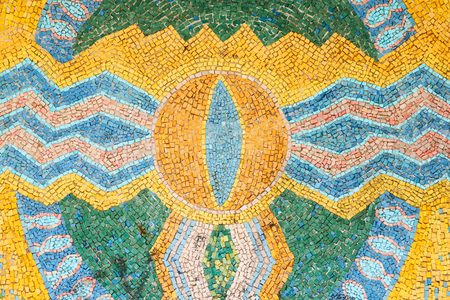 Beautiful background of multi-colored tiles. Tiled mosaic in Blue, green, yellow colors . Eye, wave, zigzag, circle, bird, star.