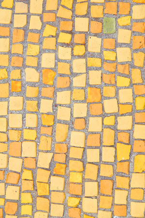 Beautiful background of multi-colored tiles. Tiled mosaic in pastel colors. Yellow, brown, orange