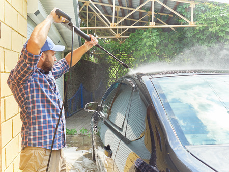 Young man washing his black car near the house