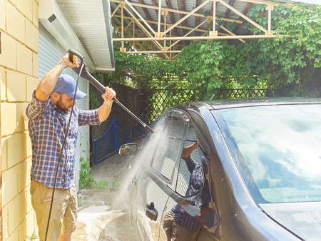 Man washing his black car near the house. Banque d'images