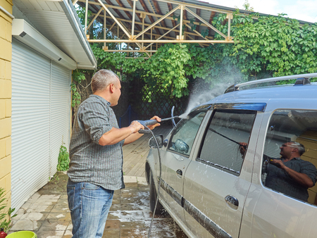 Man washing his silver car near the house.