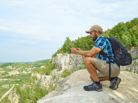 Man Tourist Uses Tablet Computer Sitting on Edge of a Cliff In Mountains.