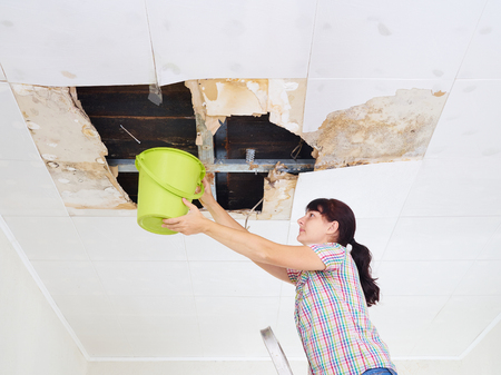 Young Woman Collecting Water In Bucket From Ceiling. Ceiling panels damaged huge hole in roof from rainwater leakage.Water damaged ceiling . Imagens - 81545786