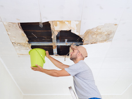 Man Collecting Water In Bucket From Ceiling. Ceiling panels damaged huge hole in roof from rainwater leakage.Water damaged ceiling . Stock Photo