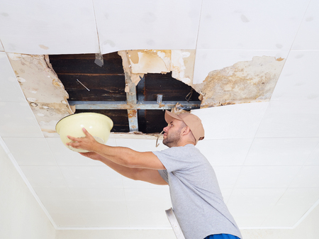 Man Collecting Water In basin From Ceiling. Ceiling panels damaged huge hole in roof from rainwater leakage.Water damaged ceiling .