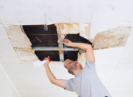 man cleaning mold on ceiling.Ceiling panels damaged huge hole in roof from rainwater leakage.Water damaged ceiling . Stockfoto